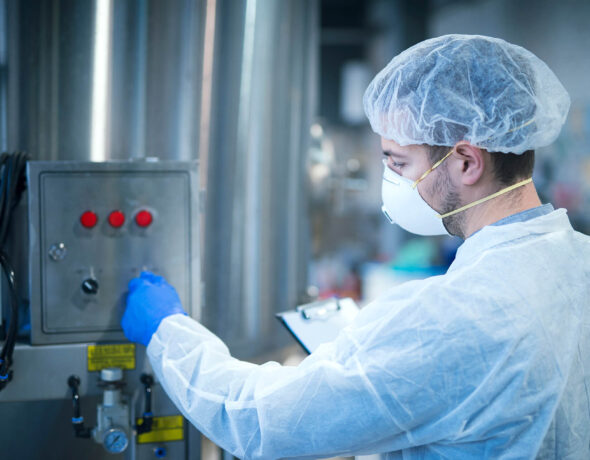 technologist-protective-uniform-operating-industrial-machine-factory-production-line